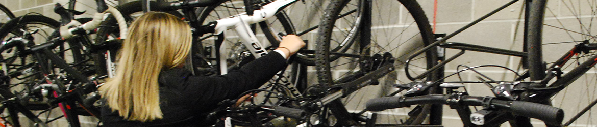 Woman Removing Bicycle from Bike Storage Area